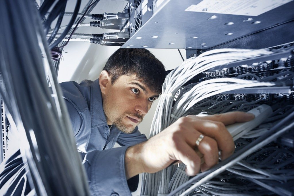 Technician is checking server's wires in data center