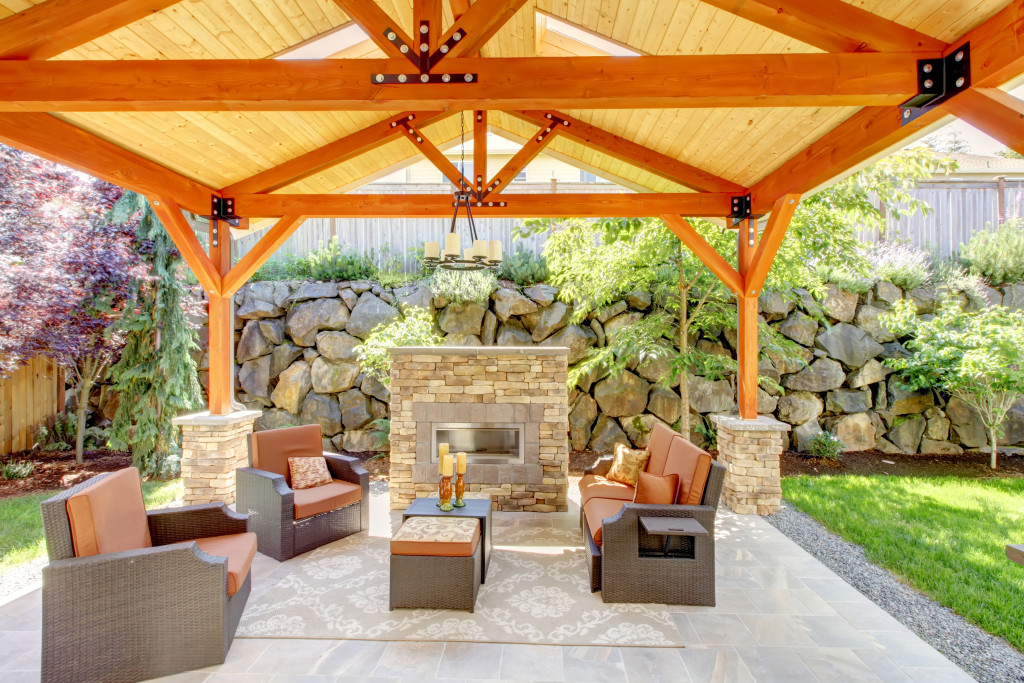 covered patio with fireplace and furniture